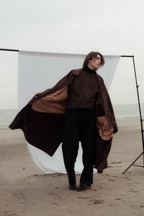 Melancholy man model in trendy clothes standing in raised hand in pocket on sandy  beach near ocean against white fabric background in cloudy day