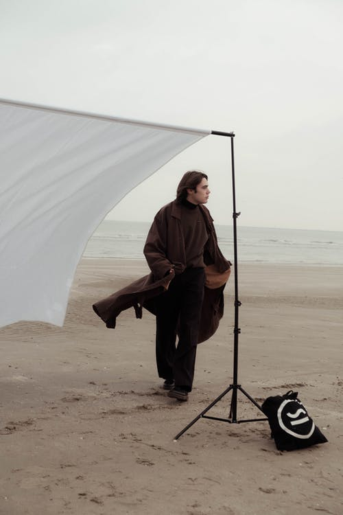 Man walking on sandy beach during photo session
