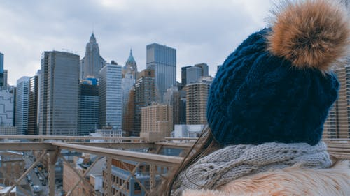Woman Wearing Bobble Hat Staring at High-rise Buildings