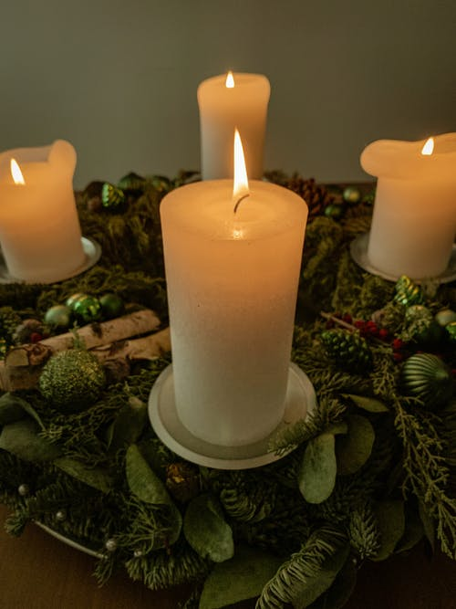 Burning candles on creative green holder