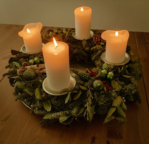 From above white thick candlesticks burning on creative wreath holder made of artificial plant leaves and placed on wooden table in dark room