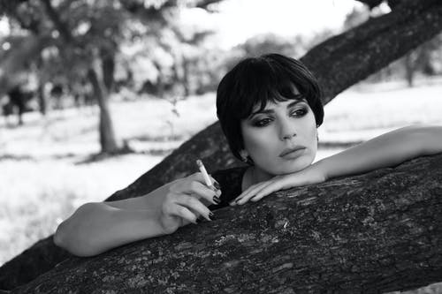 Black and white of pensive woman with dark hair leaning on tree while smoking cigarette and thoughtfully looking away in park in daytime