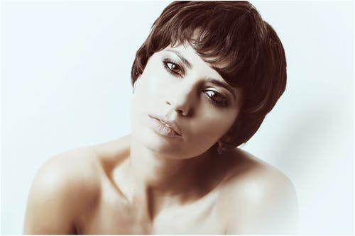Sensual woman with bare shoulders looking at camera against light background