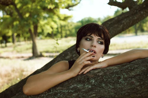 Thoughtful woman smoking cigarette in nature in daytime