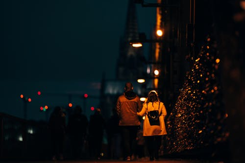 A Couple Walking On Sidewalk Of A Street During Night Time