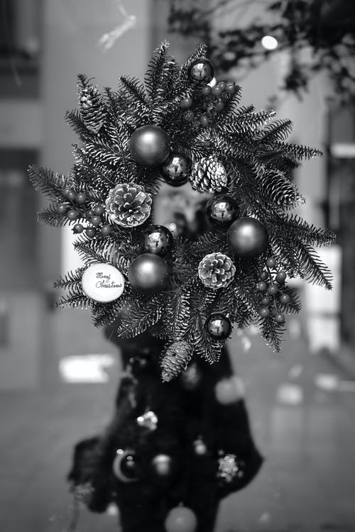 Black and white of Christmas wreath decorated with small shiny baubles and pine cones hanging on door of modern building during festive event