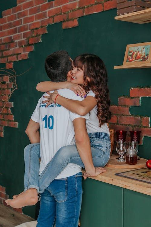 Happy Asian woman embracing boyfriend gently