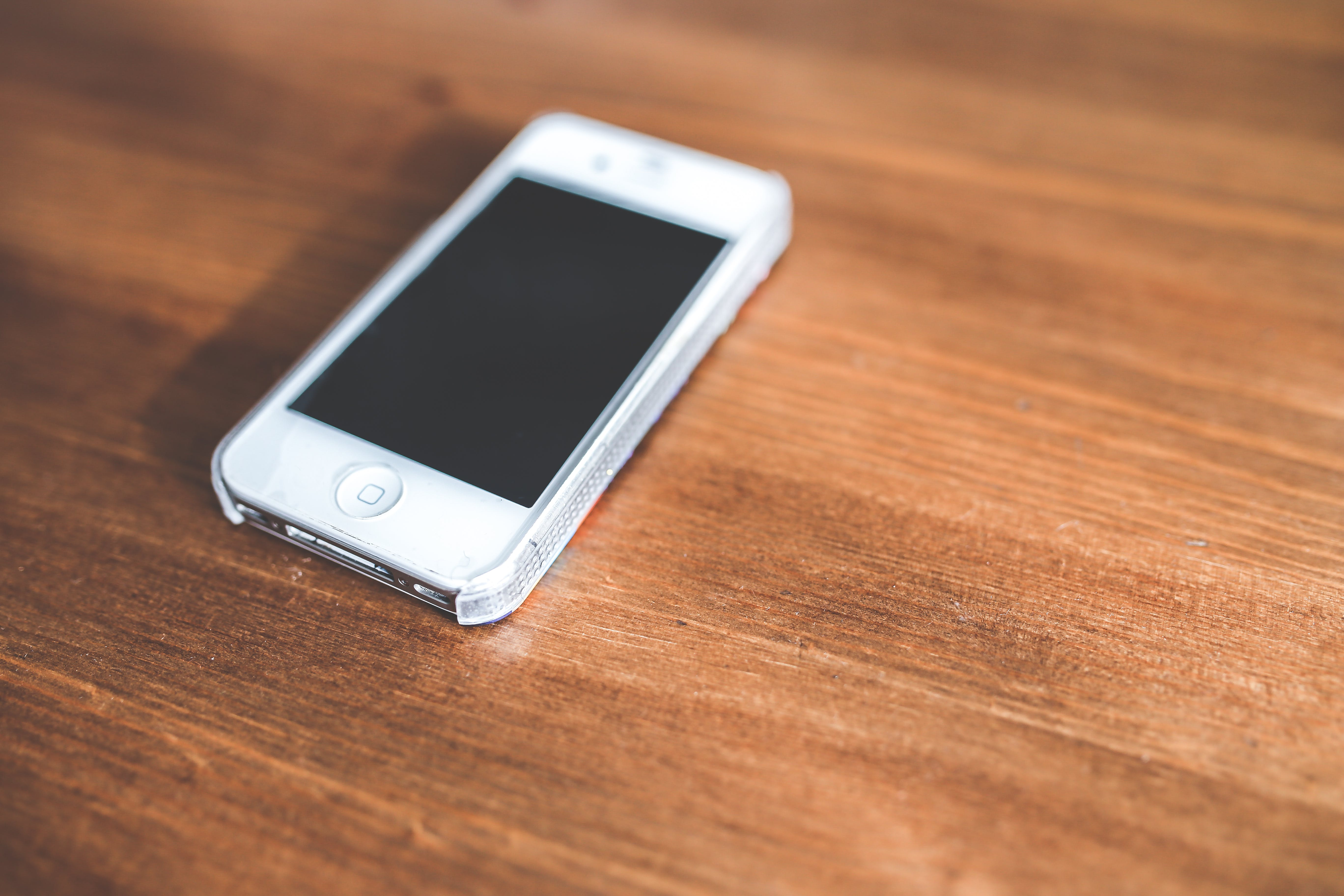 White iPhone 4/4s on a wooden table