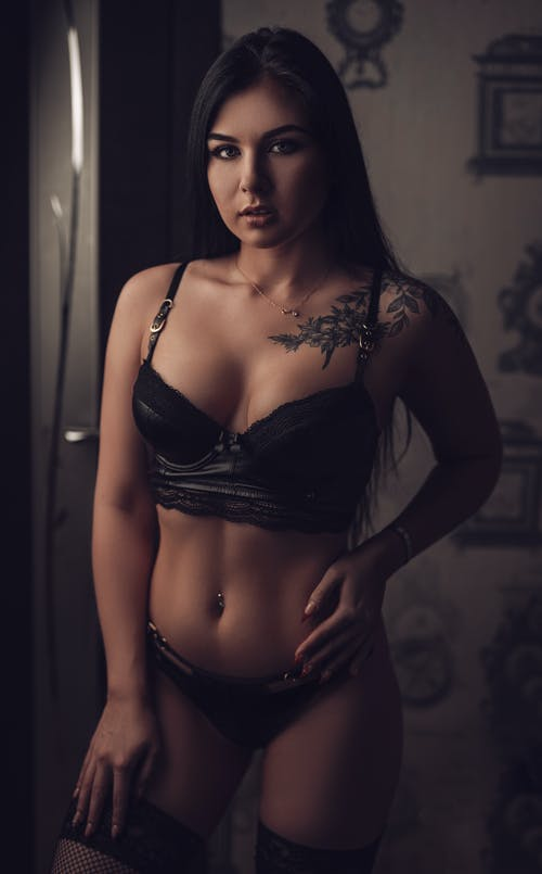 Tattooed model in lingerie touching thigh at home