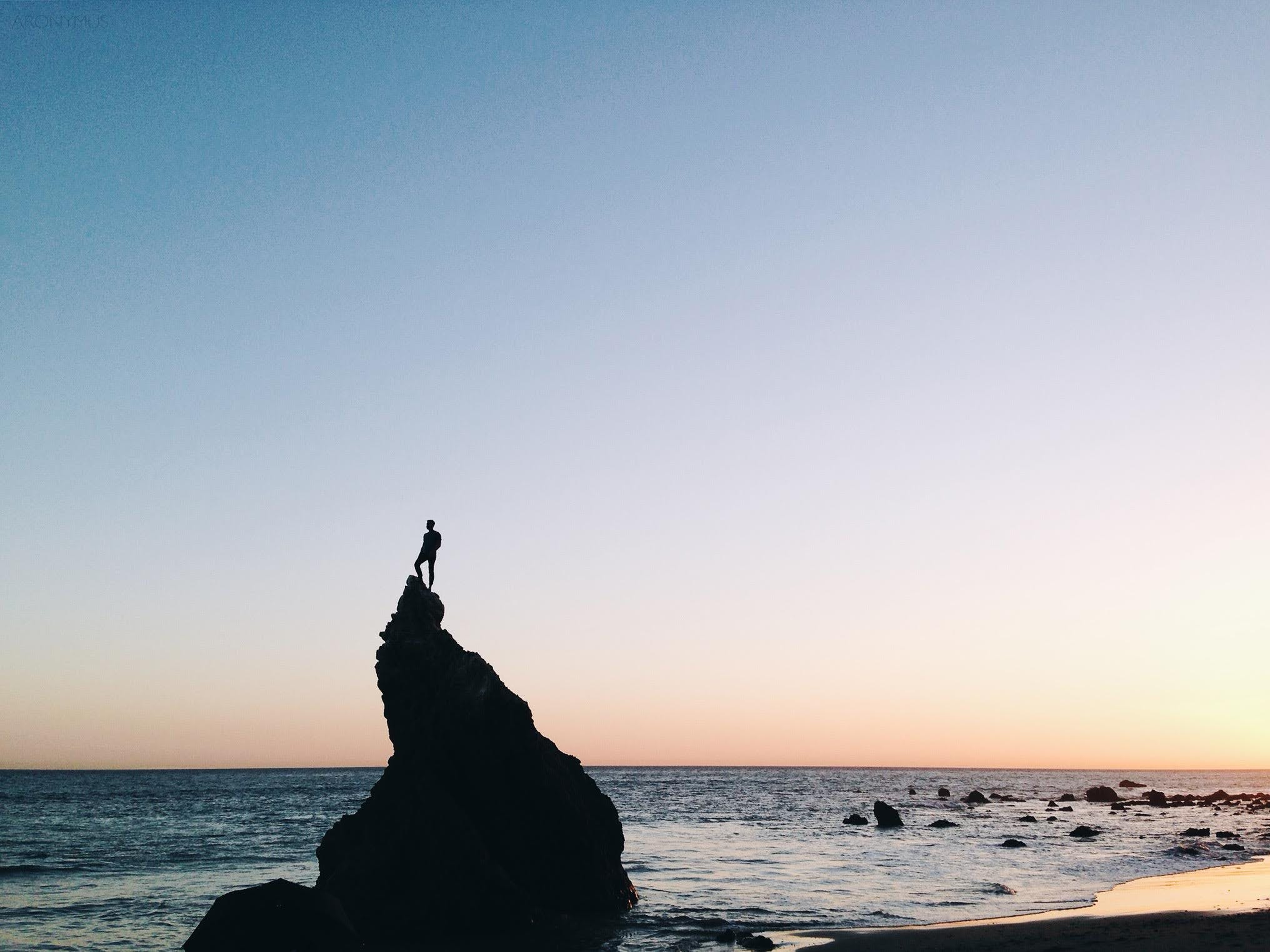 Silhouette of Person Standing on Rock on Beach Shore during Yellow Sunset