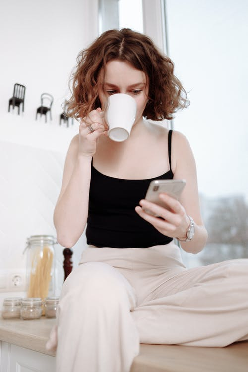 Woman in Black Tank Top and White Pants Drinking from White Ceramic Mug