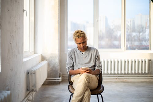 Young concentrated African American male looking at screen of mobile phone on chair in spacious room