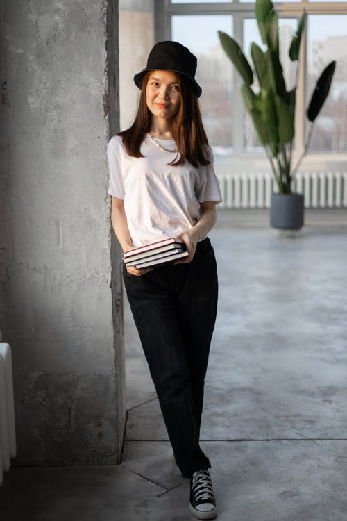 Woman in White Crew Neck T-shirt and Black Pants Holding Book