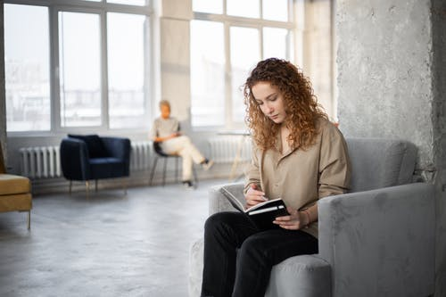 женщина в коричневом пальто, сидящая на сером диване кресле