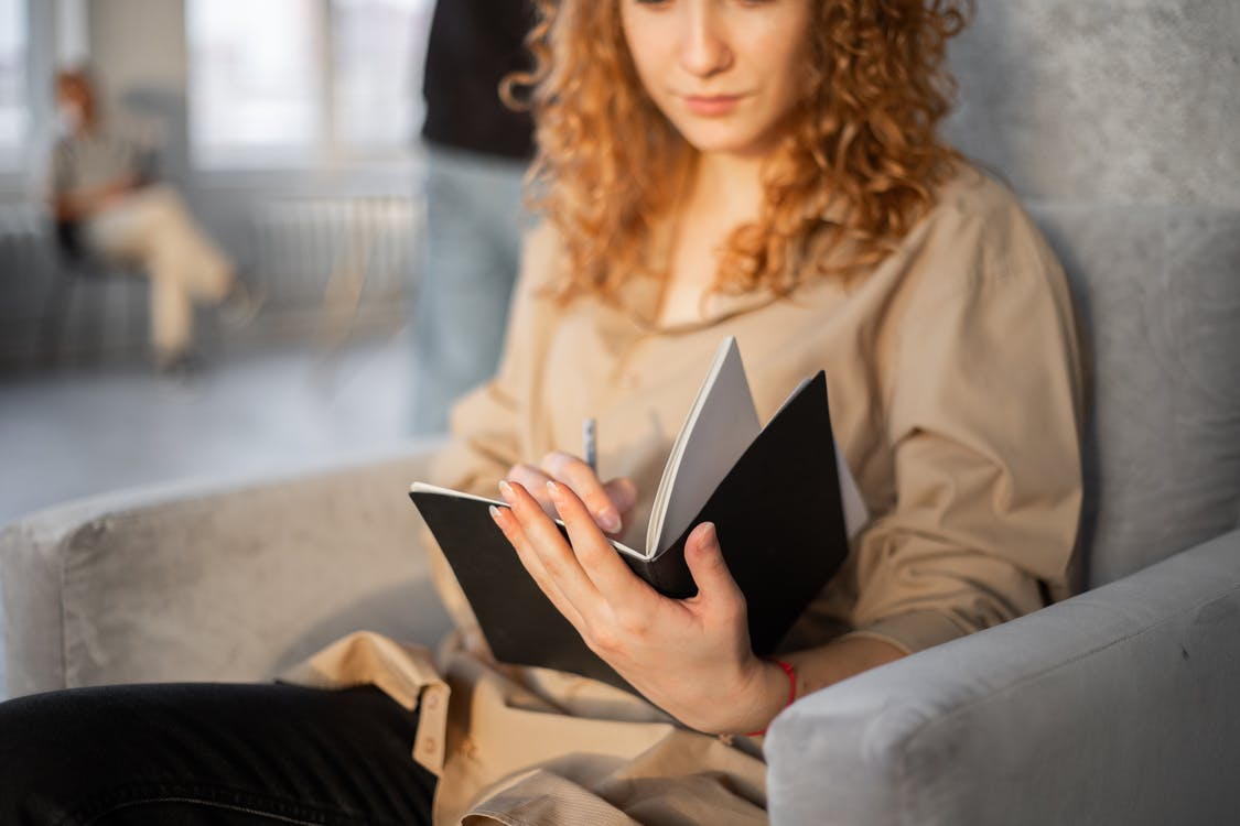 Young crop anonymous female with pen taking notes in planner while resting in soft gray armchair on blurred background
