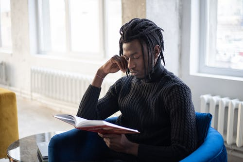 Young pensive black man with dreadlocks reading book
