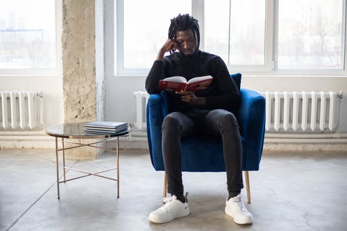 Full body of young African American male reading book in comfortable armchair near table with literature in hall in daytime