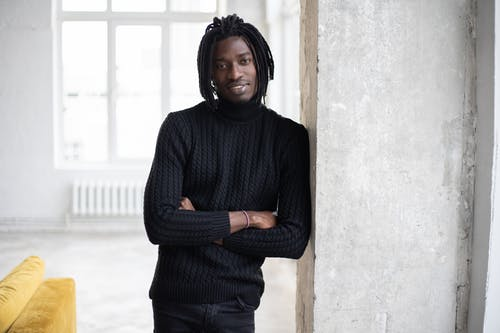 Cheerful black man with dreadlocks leaning on door and looking at camera
