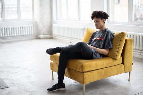 Pensive African American guy with curly hair in casual clothes reading book while sitting with crossed legs on yellow comfortable armchair in light studio in daytime