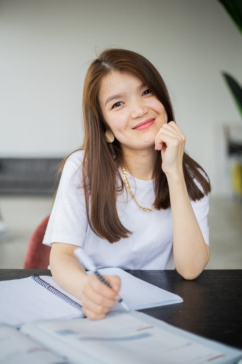 Cheerful Asian woman with pen studying in room