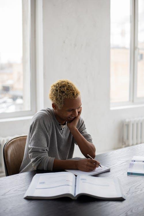 Cheerful black man writing in copybook