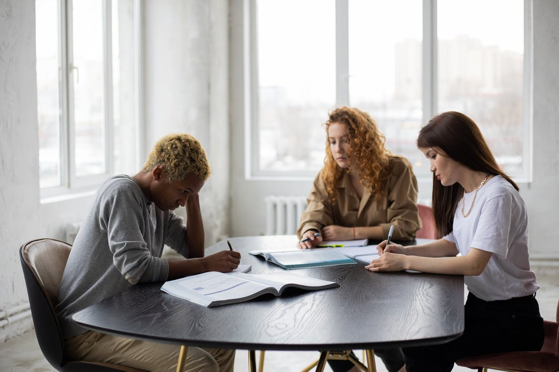Group of focused multiracial classmates taking notes in notebooks while collaborating during preparation for lesson at wooden table with textbook
