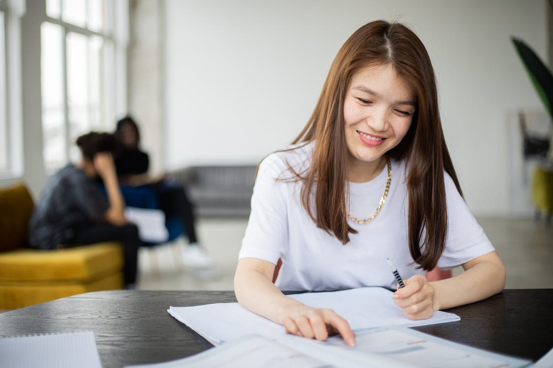 Smiling Asian female with pen and copybook reading textbook at table during lesson in room with classmates on blurred background