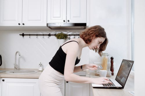 Woman in Black Tank Top and White Pants Holding Silver Laptop Computer