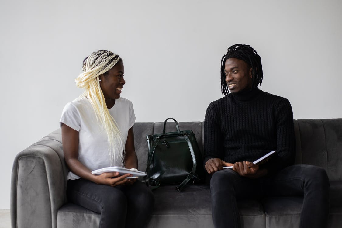 Cheerful black students with copybooks chatting on sofa