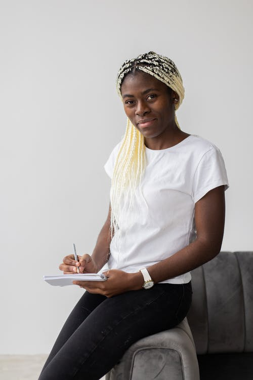 Cheerful black woman writing in notebook on sofa