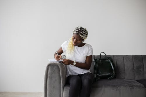 Focused African American female student with Afro braids taking notes in copybook while solving task on couch with backpack in room
