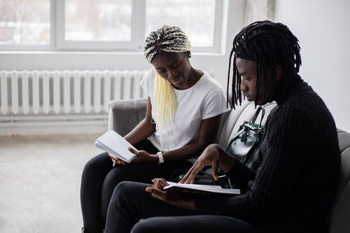 Serious African American classmates looking at notes in notebooks and sitting on sofa while preparing for exam in light room