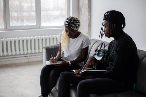 Focused black students writing in copybooks while sitting on couch