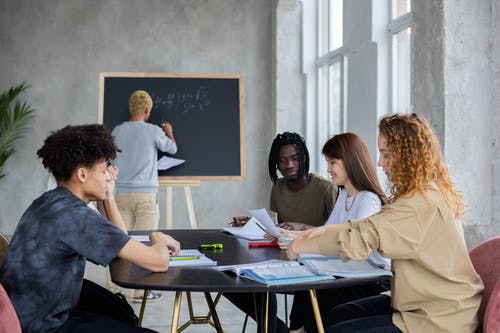 Unrecognizable male writing mathematical equation on chalkboard in classroom with group of multiethnic student at table solving task during lesson