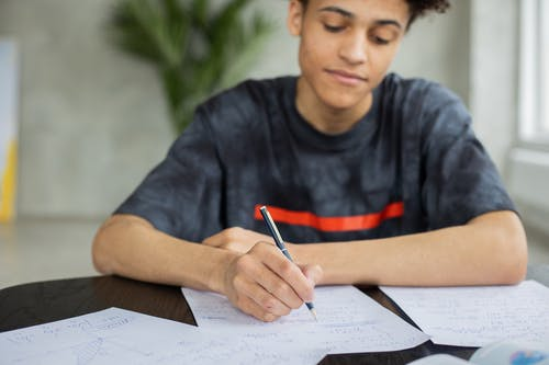 Crop African American male student taking notes on piece of paper at table while studying subject in classroom on blurred background