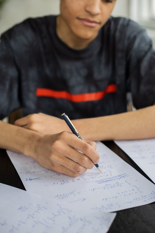 Crop black man writing on paper in classroom