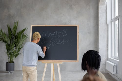 Anonymous black man writing equation on chalkboard