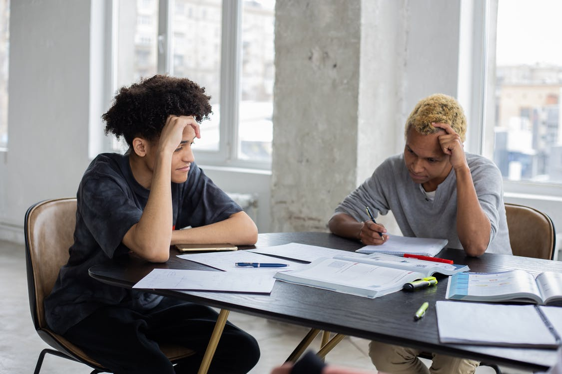Concentrated black men studying at table