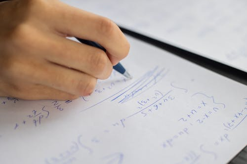 Unrecognizable smart student taking notes on piece of paper while solving mathematical formulas during lesson in classroom on blurred background