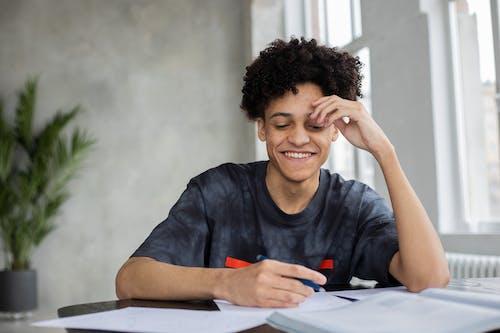 Cheerful black man writing on paper
