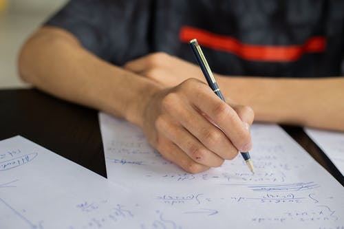 Unrecognizable smart male student with pen  taking notes while solving equations at table during lesson in classroom on blurred background