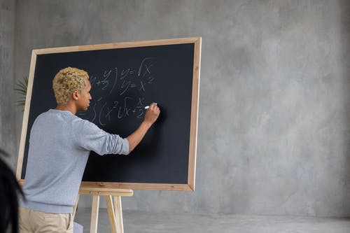 Serious black student writing mathematical example on blackboard
