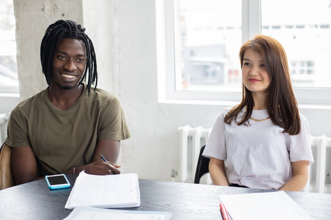 Cheerful black student sitting near classmate during studies