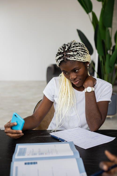 Black woman taking selfie on smartphone during studies