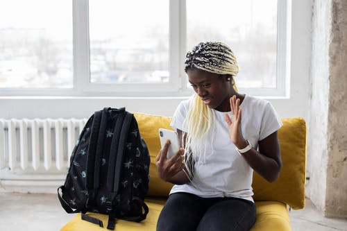 African American female in casual clothes sitting on sofa with backpack and waving hand for mobile phone during video chat
