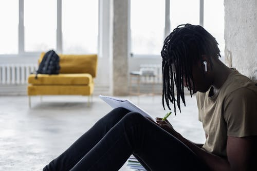 Side view of African American male student reading in notebook while doing homework in wireless earphones sitting near concrete column