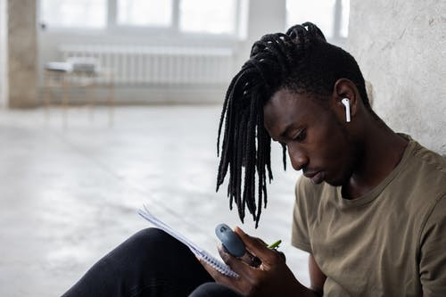 Focused black student in wireless earbuds writing in notebook