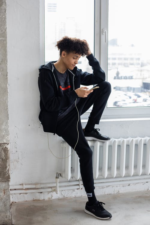 Full body of African American male with curly hair sitting near window and browsing charging mobile phone