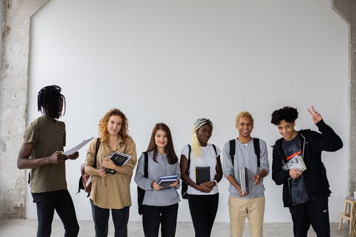 Cheerful multiethnic students with notepads and textbooks together