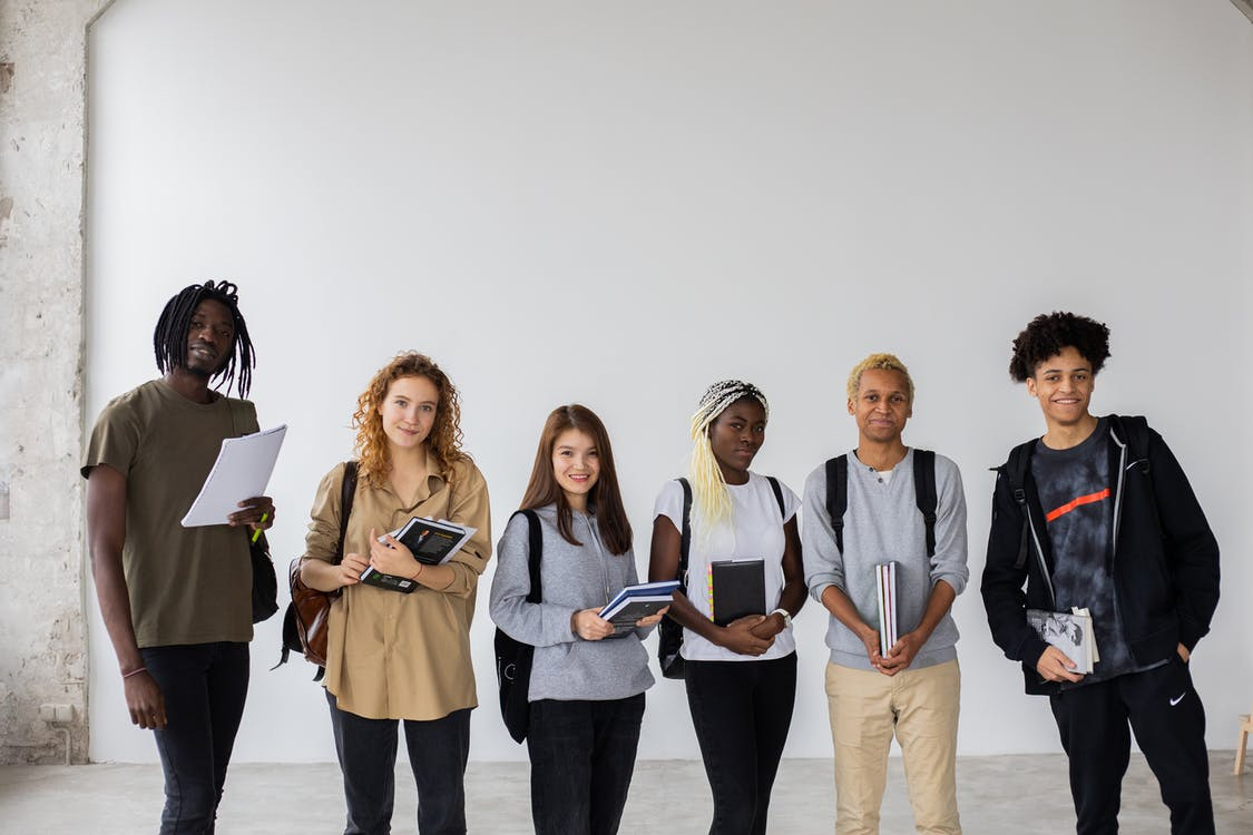 Group of diverse young multiracial classmates with notebooks and textbooks and backpacks smiling at camera